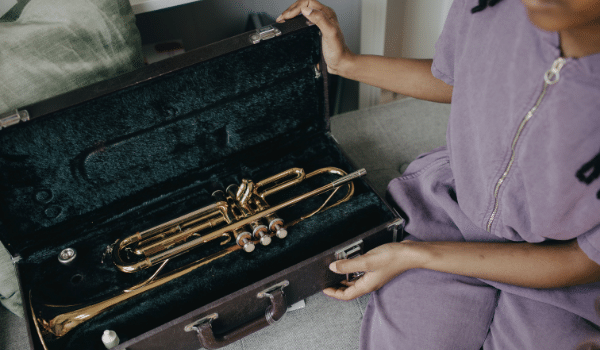 a girl preparing her musical instrument for the move
